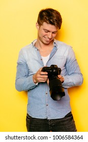 Smiling photographer in jeans shirt checking photos in the digital camera.