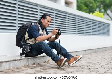 Smiling photographer looking at the photos on his digital camera