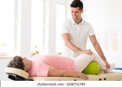 Smiling physiotherapist supporting a senior woman during rehabilitation