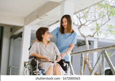 Smiling physiotherapist  taking care of the happy senior patient in wheelchair