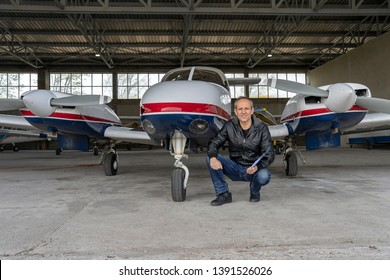 Smiling Pilot in front of Modern Private Airplane in a Hangar. Flight Instructor Going Through a Pre-Flight Pilot Checklist. Confident Pilot Holding Clipboard and Looking at Camera.