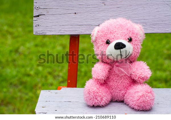 smiling pink teddy bear looks very happy sitting on a vintage bench