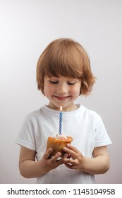 smiling pleasant kid has got a cake on birthday. close up photo. happiness and magic time concept