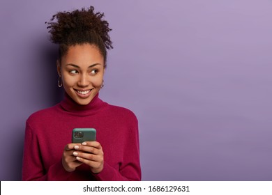 Smiling pleasant looking woman receives message from dating app, holds mobile phone in hands, looks happily aside, edits photo to post online, has curly hair, isolated on violet wall, copy space