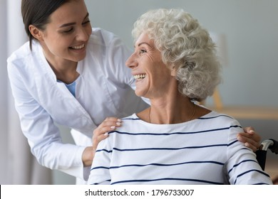 Smiling pleasant young medical worker in white uniform supporting happy middle aged handicapped woman in wheelchair, headshot. Retirement disability healthcare, rehabilitation medical service concept.
