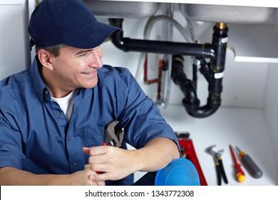 Smiling plumber repairs a sink.