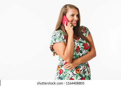 Smiling plus size girl in colorful dress happily talking on cellphone looking aside isolated