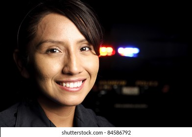 a smiling police officer with her patrol unit in the background with its lights on.