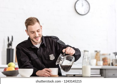 smiling police officer pouring filtered coffee from glass pot at kitchen