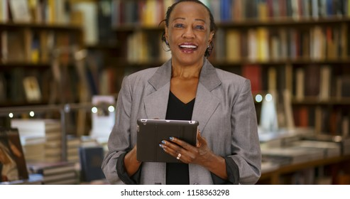 Smiling portrait of African American woman using digital tablet inside bookstore