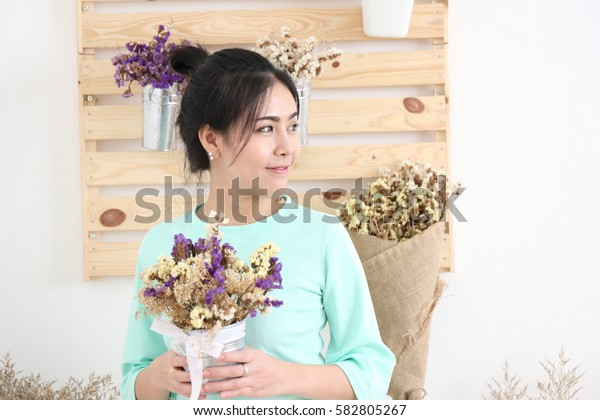 Smiling portrait of an attractive florist business Asian woman owner at a flower shop market working and making a new floral arrangement during a sunny day. Small business owner.
