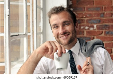 smiling portrait of an attractive man next to window