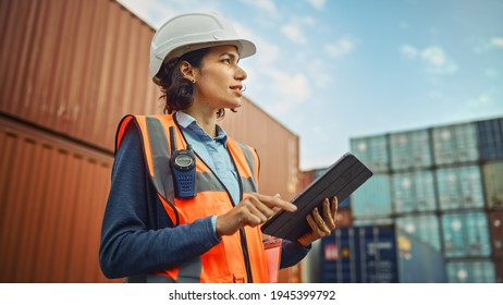 Smiling Portrait of a Beautiful Latin Female Industrial Engineer in White Hard Hat, High-Visibility Vest Working on Tablet Computer. Inspector or Safety Supervisor in Container Terminal.