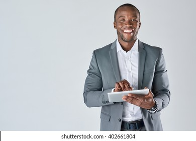 Smiling portrait of black businessman with touchscreen tablet device in business suit isolated in studio