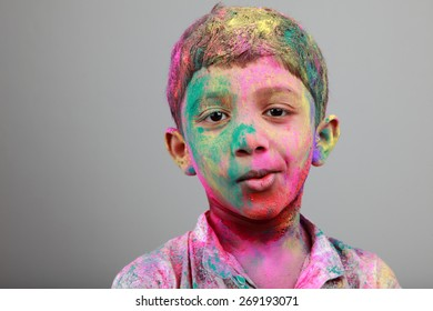 Smiling Portrait of boy with face smeared with colored powder. Concept for festival Holi