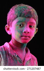 Smiling Portrait of boy with face smeared with colored powder in a dark background. Concept for Indian festival Holi.