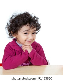Smiling portrait of a Cute Baby Girl Sitting at a Desk, Isolated, White