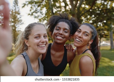 Smiling portrait of diverse female friends looking at camera taking selfie in park - fitness friends taking a selfie after exercising