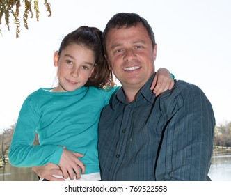 Smiling portrait of a father and daughter outdoors during holidays