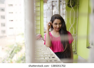 Smiling portrait of an Indian Bengali beautiful and young girl in western dress standing in front of a balcony with ample light leaning on the balcony grill wall. Indian lifestyle