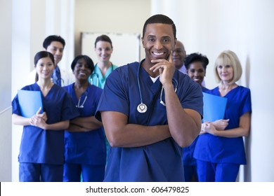 Smiling portrait male African American nurse with multi ethnic professional specialist surgical team in hospital facility