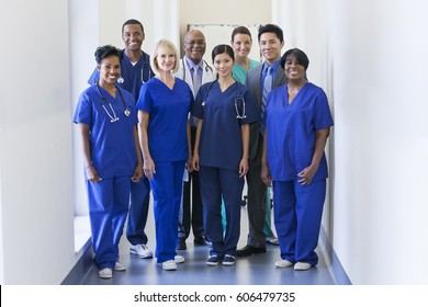Smiling portrait multi ethnic team in uniform providing healthcare treatment and patient diagnosis in modern medical facility