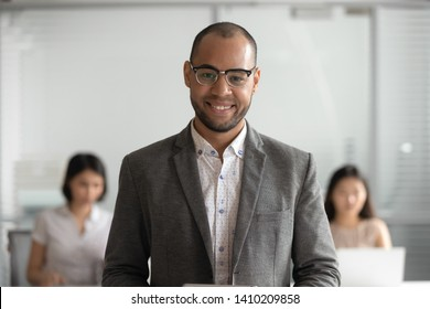 Smiling positive african american business man in suit looking at camera in corporate office, successful team leader, company boss manager, mixed race millennial executive, happy male coach portrait