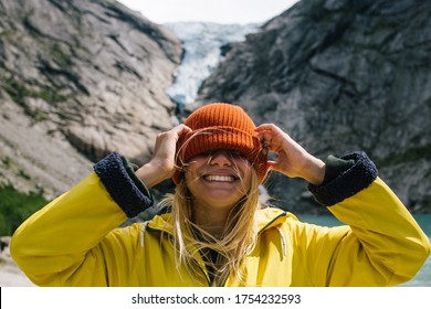 Smiling, positive blonde woman with wild hair puts a hat on her face on background of blue ice tongue of Briksdal glacier that slides from the giant rocky mountain and melts into cold lake in Norway