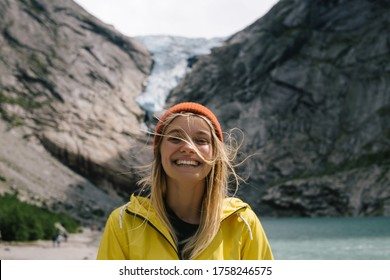 Smiling, positive blonde woman with wild hair in full face on background of blue ice tongue of Briksdal glacier that slides from the giant rocky mountain and melts into cold lake in Norway