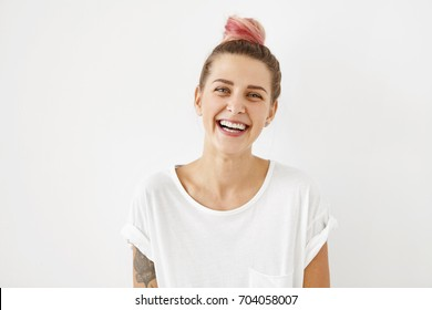 Smiling positive female with attractive look, wearing loose white T-shirt, posing against white blank wall. Happy woman with hair bun showing positive emotions after receiving pleasant compliment