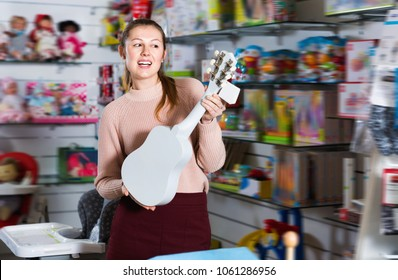 Smiling positive  female consumer holding toy guitar in the children's store