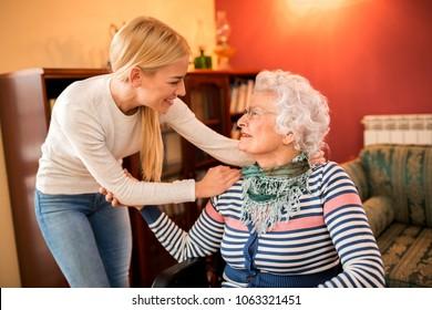Smiling positive granddaughter visit her sick grandma at home
