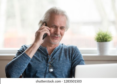 Smiling positive grey haired old senior man sitting opposite computer holding gadget making business or informal call talking on mobile phone. Old people and modern technologies easy using concept