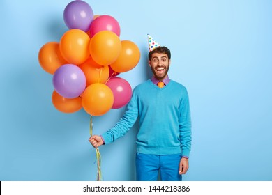 Smiling positive guy holds bunch of colorful helium balloons, wears holiday cap and blue clothes, comes on birthday party, isolated on blue background. Event manager poses with festive accessory