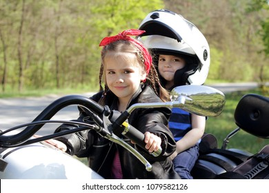 Smiling positive little boy with his elder sister in leather jacket riding the motorbike in the early spring park, happy family weekend, outdoor portrait, extreme adventures and safety