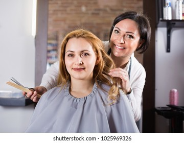 Smiling positive young blonde woman very much likes her fashionable hairdress in hairdressing salon