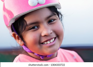 Smiling pre teen kid of mixed ethnicity, with a healthy full set of teeth and wearing a pink bicycle helmet.