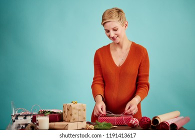Smiling pregnant saler preparing presents for clients at her gift shop at christmas time making a bow on red gift box, isolated at studio over blue background