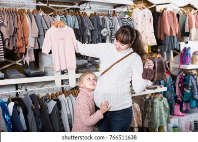Smiling pregnant woman and child searching clothes for newborn in children`s cloths shop