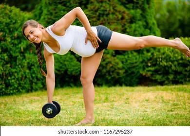 Smiling Pregnant Woman Doing Single Leg Dumbbell Deadlift In Par