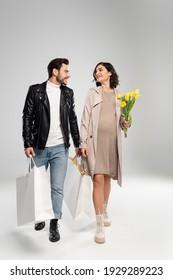Lächelnde schwangere Frau mit Blumen, die beim Ehemann mit Einkaufstaschen auf grauem Hintergrund geht
