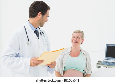 Smiling pregnant woman having a check up with doctor at the hospital