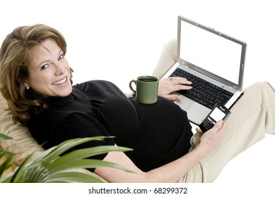 smiling pregnant woman in her 40's, with laptop, and phone, casual clothing, coffe cup on belly, blank screens