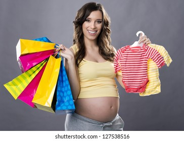 Smiling pregnant woman holding shopping bags