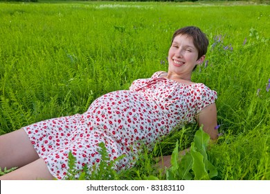 Smiling pregnant woman lie on the grass