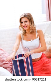 Smiling pregnant woman sitting on couch and opening shopping bag