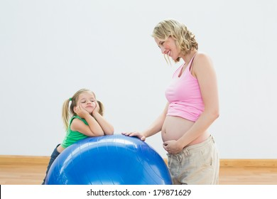 Smiling pregnant woman with young daughter in a fitness studio