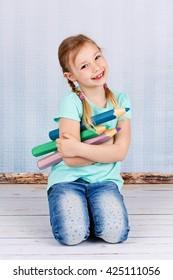 Smiling preschool girl holding big crayons