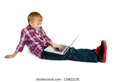 A smiling pre-teen boy sitting with a laptop computer on his lap