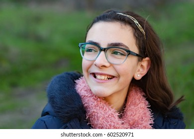 Smiling preteen girl in the garden at winter